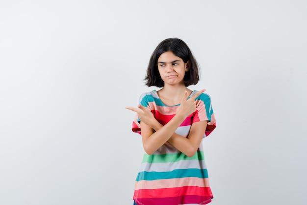 カラフルなストライプのtシャツで反対方向を指し、物思いにふける、正面図を探している若い女の子。