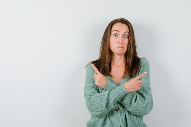 Young girl pointing opposite directions with index finger in knitwear, skirt and looking scared. front view.