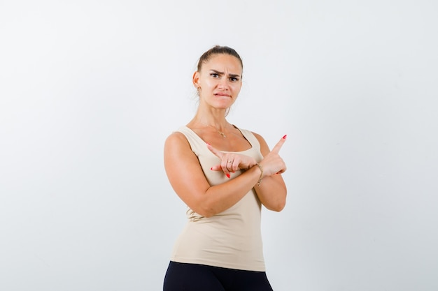 Young girl pointing opposite directions with index fingers in beige top, black pants and looking anxious