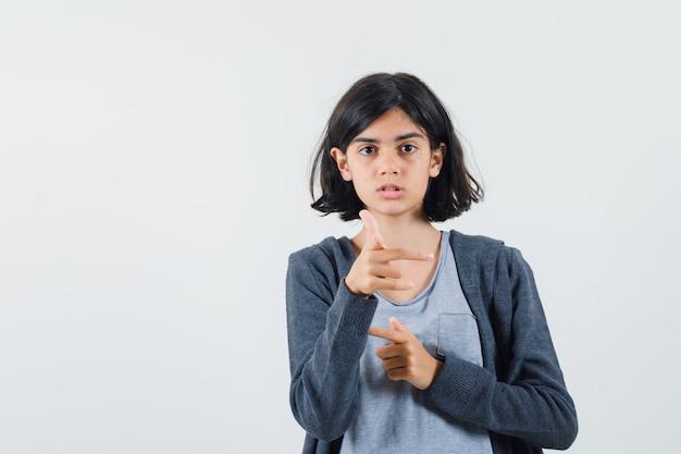 Молодая девушка в светло-серой футболке и темно-серой толстовке с капюшоном на молнии, показывающая в противоположных направлениях указательными пальцами, выглядит мило.
