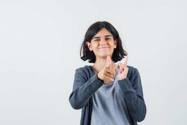 Молодая девушка в светло-серой футболке и темно-серой толстовке с капюшоном на молнии, указывая указательными пальцами в противоположных направлениях, выглядит счастливой.