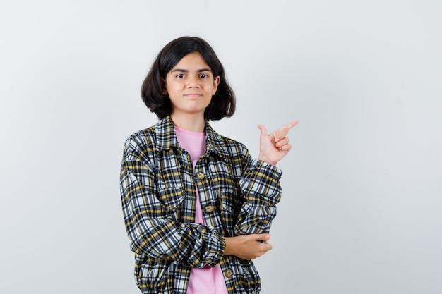 오른쪽을 가리키고 체크 셔츠와 분홍색 티셔츠를 입은 팔꿈치에 한 손을 잡고 귀엽게 보이는 어린 소녀. 전면보기.