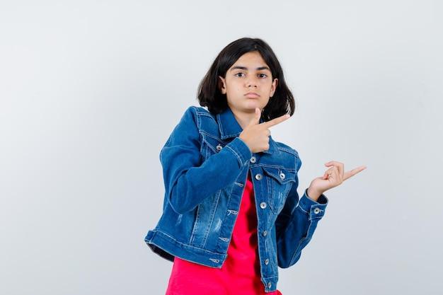 Giovane ragazza che punta a destra in maglietta rossa e giacca di jeans e sembra carina.
