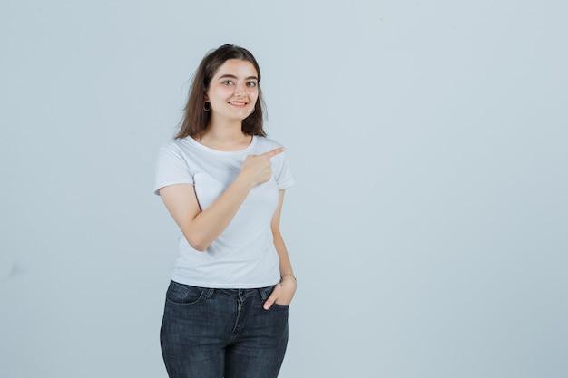 Giovane ragazza che punta a destra in t-shirt, jeans e che sembra felice, vista frontale.