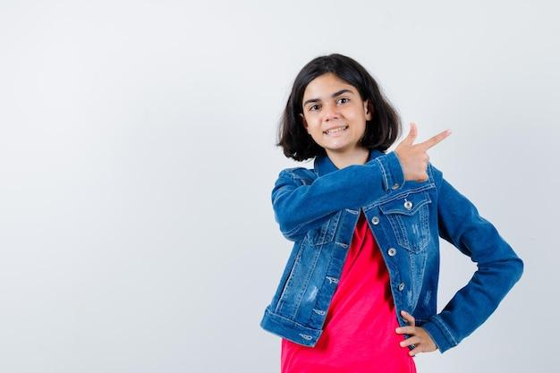Giovane ragazza che punta a destra mentre tiene la mano sulla vita in maglietta rossa e giacca di jeans e sembra felice.