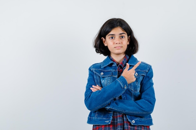 체크 셔츠와 진 재킷에 검지 손가락으로 오른쪽을 가리키고 예쁘게 보이는 어린 소녀. 전면보기.