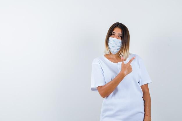 흰색 t- 셔츠와 마스크에 검지 손가락으로 오른쪽을 가리키고 자신감, 전면보기를 찾고 어린 소녀.