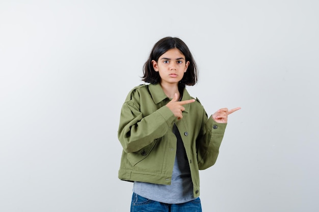 Young girl pointing right with index fingers in grey sweater, khaki jacket, jean pant and looking serious , front view.