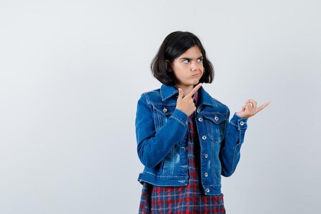 Молодая девушка указывает вправо указательными пальцами в клетчатой рубашке и джинсовой куртке и выглядит мило, вид спереди.