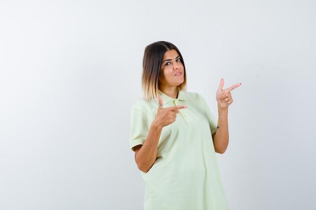 Tシャツの人差し指で右を指し、自信を持って、正面図を探している若い女の子。