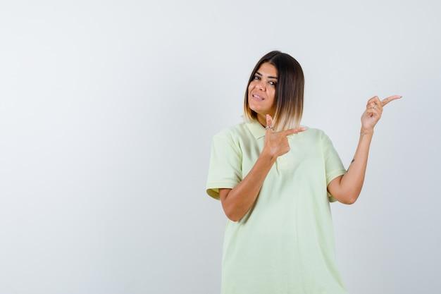 Tシャツの人差し指で右を指して陽気に見える少女。正面図。