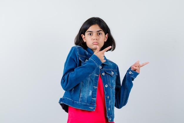 Giovane ragazza che punta a destra con l'indice in maglietta rossa e giacca di jeans e sembra carina, vista frontale.
