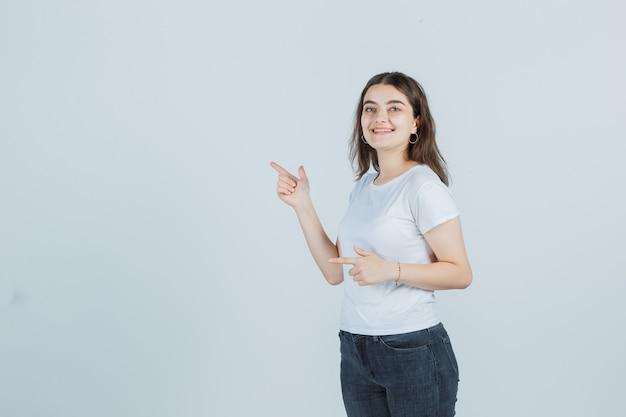 Ragazza che punta al lato in t-shirt, jeans e che sembra allegra. vista frontale.