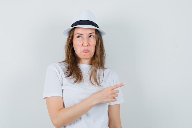 Ragazza che punta al lato in maglietta bianca, cappello e sguardo offeso. vista frontale.