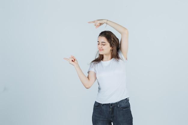 어린 소녀는 측면을 가리키고, 티셔츠, 청바지를 내려다보고 기쁘게 생각합니다. 전면보기.