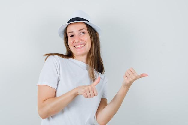 白いtシャツ、帽子、嬉しそうに見える、正面図で親指で横を指している若い女の子。