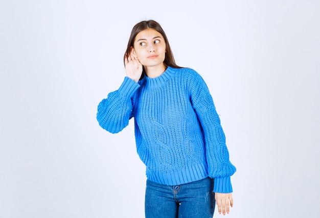 Giovane ragazza che punta cercando di ascoltare qualcosa su bianco.