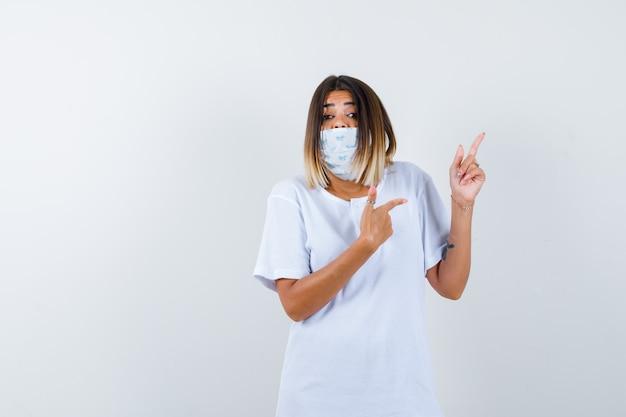 어린 소녀 흰색 t- 셔츠, 마스크 및 흥분 찾고 검지 손가락으로 위쪽 및 오른쪽을 가리키는. 전면보기.