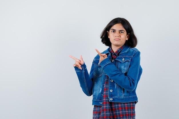 Giovane ragazza che indica in camicia a quadri e giacca di jeans e sembra carina. vista frontale.
