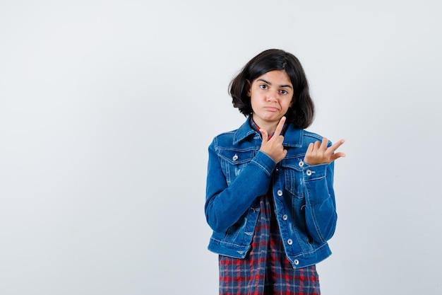 Молодая девушка указывает вверх в клетчатой рубашке и джинсовой куртке и выглядит серьезно