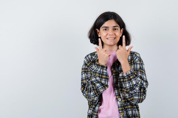 체크 셔츠와 분홍색 티셔츠를 입고 예쁘게 보이는 어린 소녀. 전면보기.