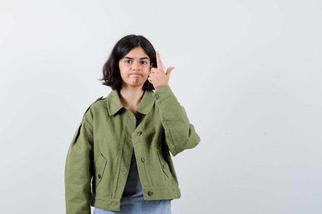 Молодая девушка указывает вверх в сером свитере, куртке цвета хаки, джинсовых брюках и выглядит серьезной. передний план.