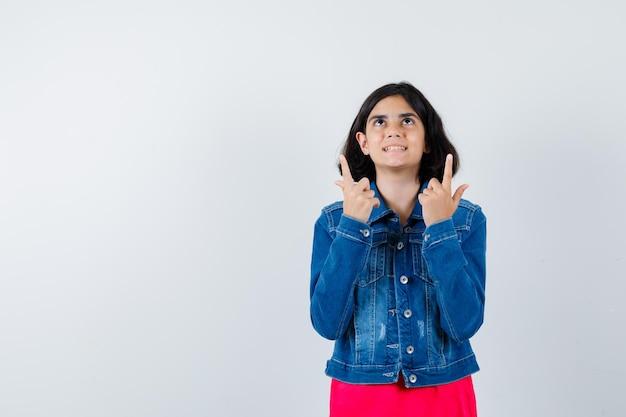 Молодая девушка указывая вверх в красной футболке и джинсовой куртке и выглядит счастливым, вид спереди.