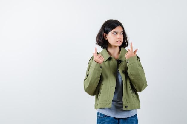 若い女の子が上を向いて、灰色のセーター、カーキ色のジャケット、ジーンズのパンツで目をそらし、かわいく見える、正面図。
