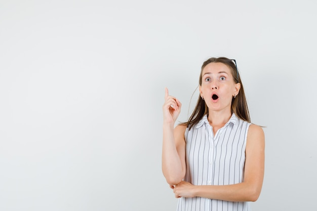 Giovane ragazza rivolta verso l'alto in t-shirt e guardando sorpreso. vista frontale.