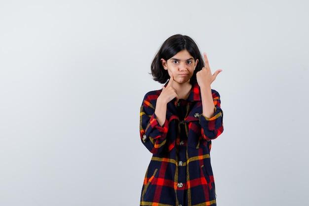 Giovane ragazza che punta verso l'alto mentre controlla la pelle in camicia a quadri e sembra carina, vista frontale.