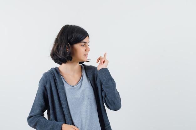 Молодая девушка указывает вверх указательным пальцем, глядя в сторону, в светло-серой футболке и темно-сером худи на молнии и выглядит мило