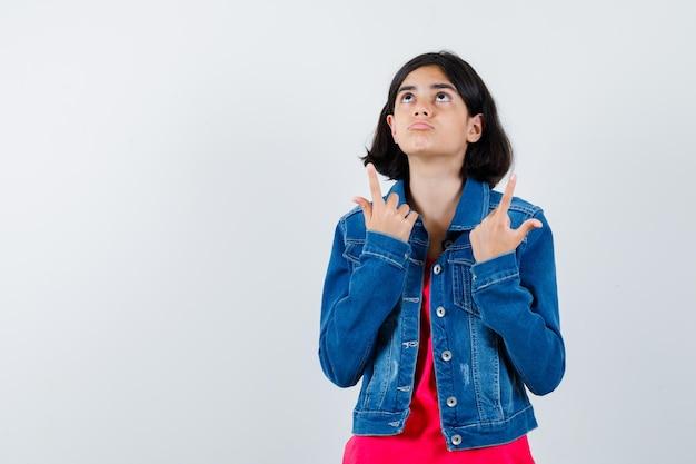 Giovane ragazza che indica con l'indice in maglietta rossa e giacca di jeans e sembra carina. vista frontale.