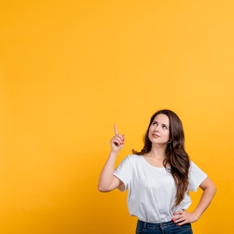 Young girl pointing up on yellow background