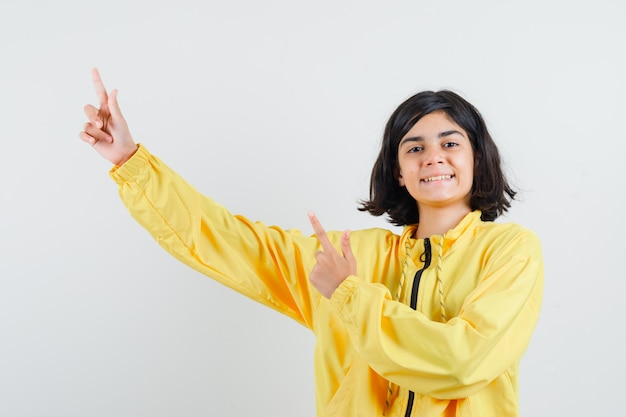 黄色のボンバージャケットの人差し指で左上隅を指して幸せそうに見える少女