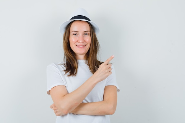 Young girl pointing at upper right corner in white t-shirt, hat and looking confident , front view.