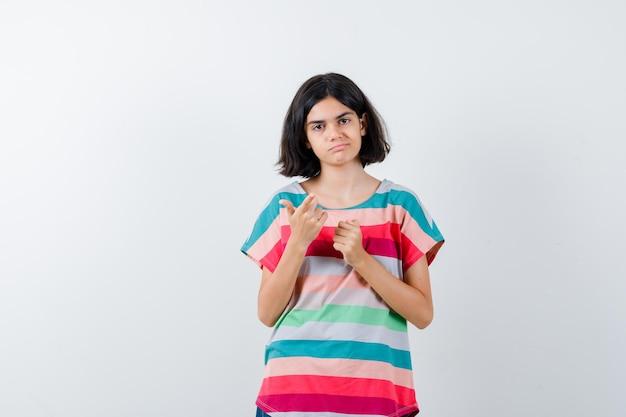 Giovane ragazza che indica con l'indice e stringe il pugno in una maglietta a righe colorata e sembra seria. vista frontale.