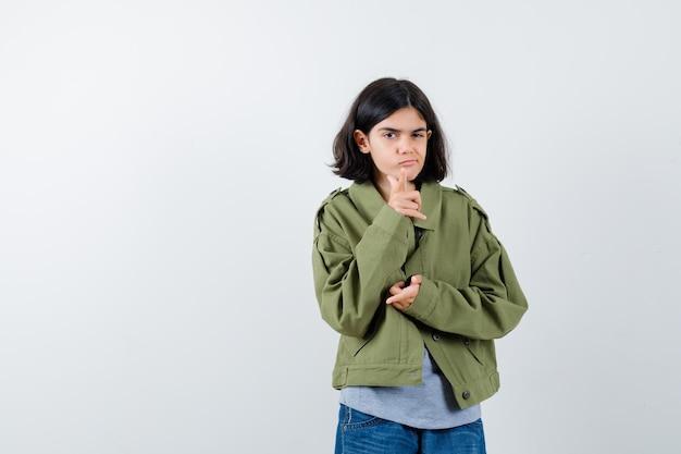 Giovane ragazza che indica con l'indice, strizza l'occhio in maglione grigio, giacca color kaki, pantaloni di jeans e sembra seria. vista frontale.