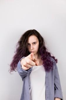 若い女の子はレンズ、深刻な顔で指を指します。紫色の髪を着色します。灰色の壁
