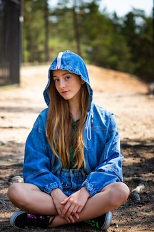 A young girl poses in a denim jacket with a hood against the of a forest sitting