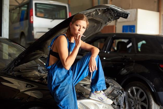 Молодая девушка позирует на капоте автомобиля и курит сигарету.