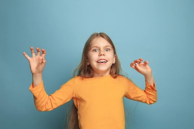 青い壁にポーズをとる少女