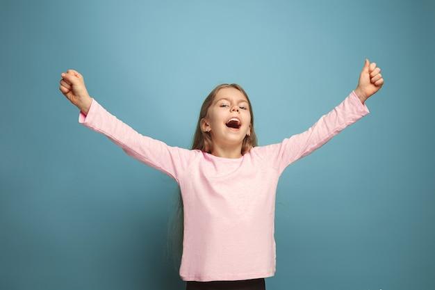 Молодая девушка позирует у синей стены