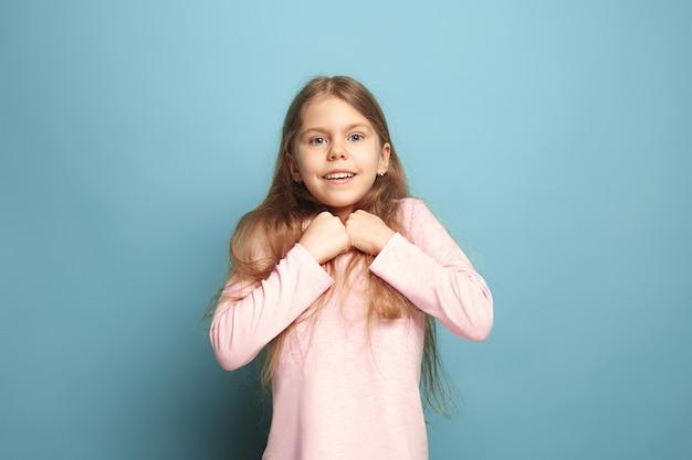 파란 벽에 포즈를 취하는 어린 소녀