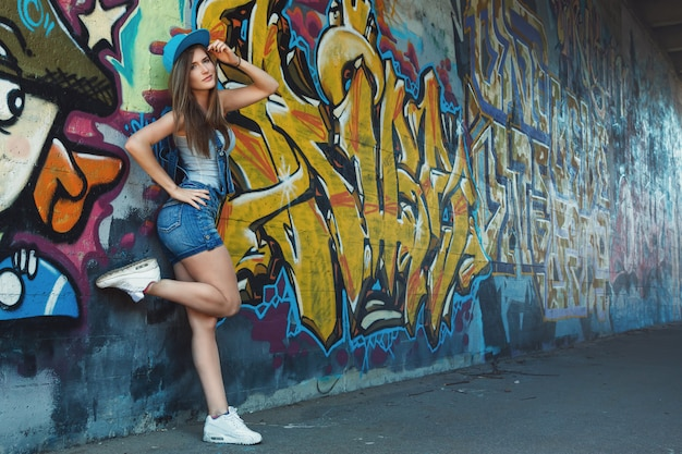 Young girl posing against wall with graffiti