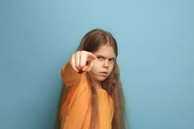 青い壁に向かってポーズをとって正面を指している若い女の子