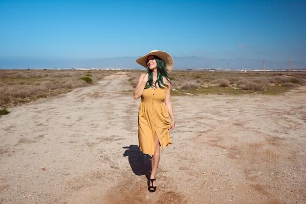 少女が砂漠で帽子でポーズします。ライフスタイルのコンセプト