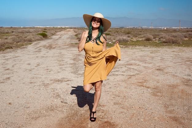 Молодая девушка позирует в шляпе в пустыне. концепция образа жизни