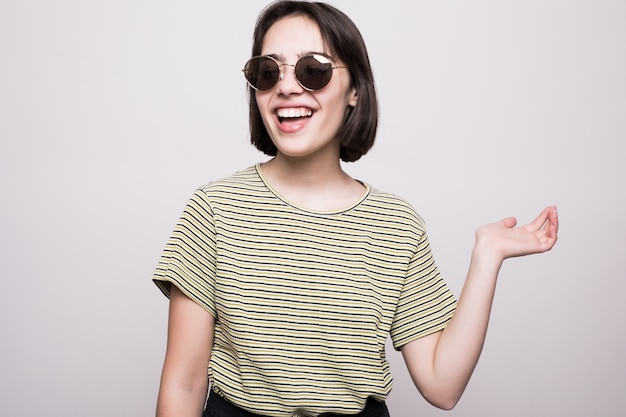 Молодая девушка позирует в солнцезащитных очках, стиль моды, изолированные на серый. женщина-хипстер