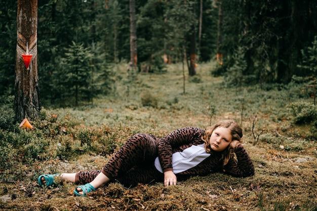 숲에서 포즈를 취하는 어린 소녀