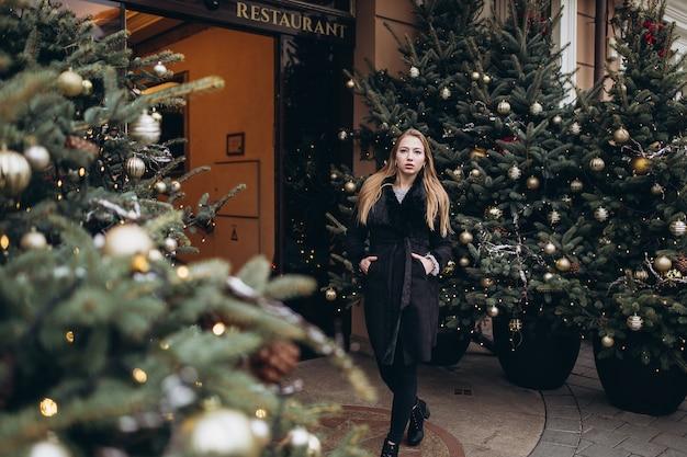 Молодая девушка позирует возле елки